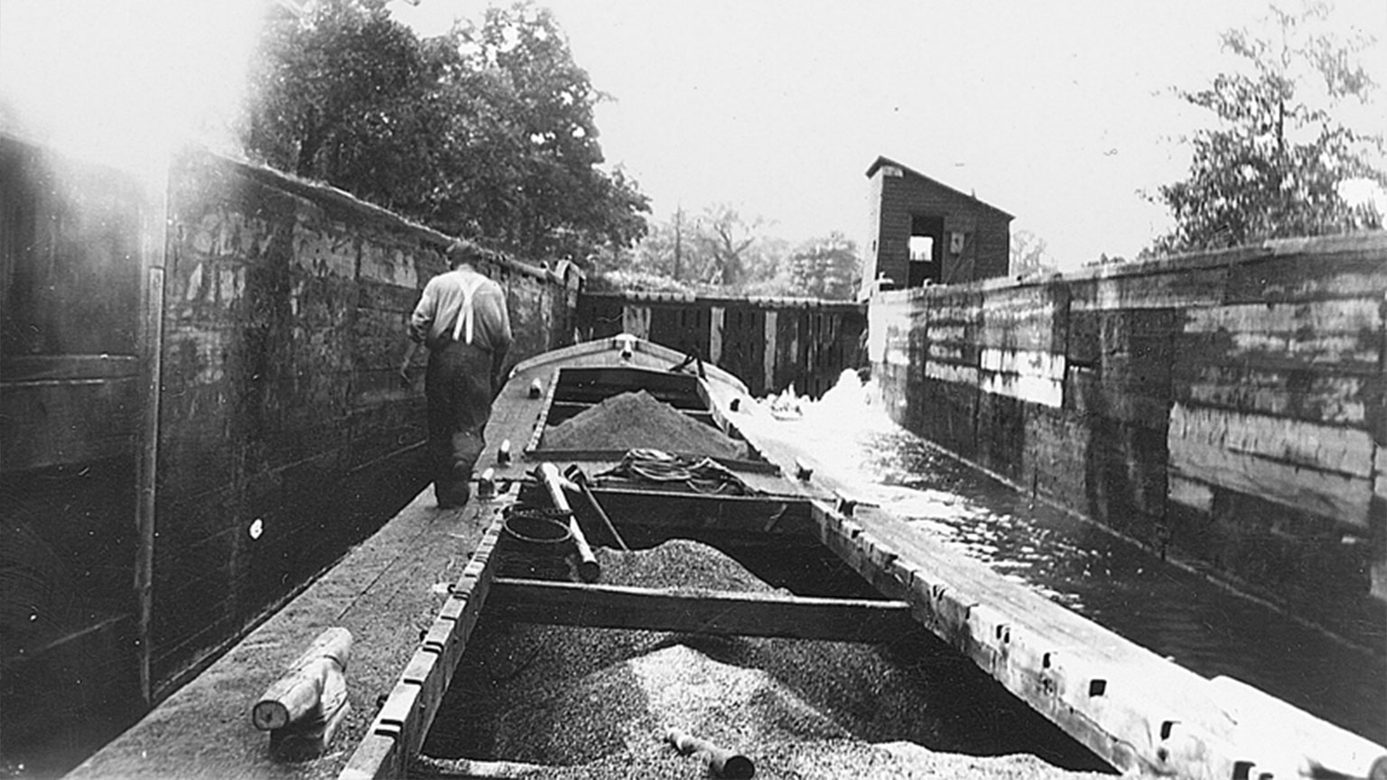 This photo shows the coal bins in his canal boat full of coal as the captain guides his boat into the lock.