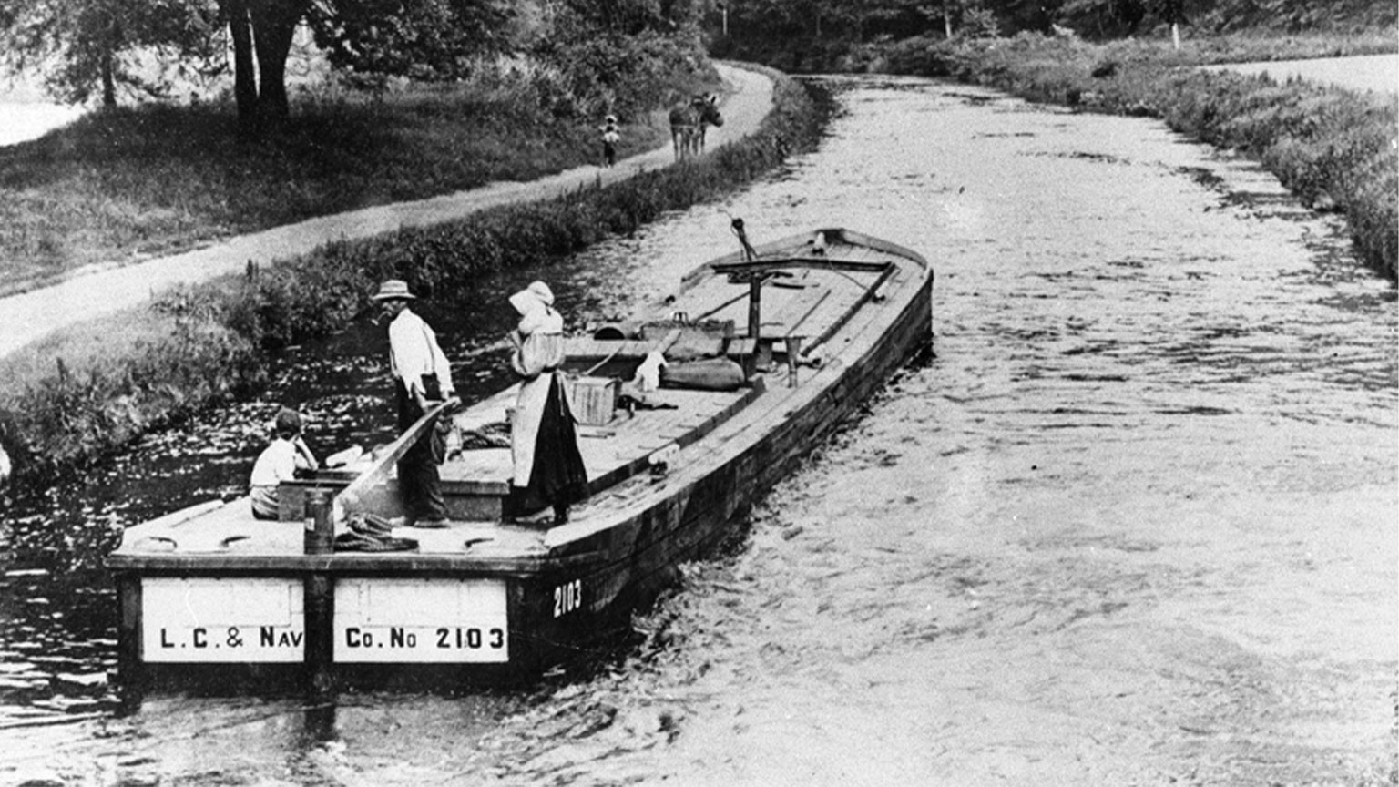 In this photo you can see the captain at the tiller, his wife and daughter on the boat and the mule tender ahead of them on the towpath with the mules.