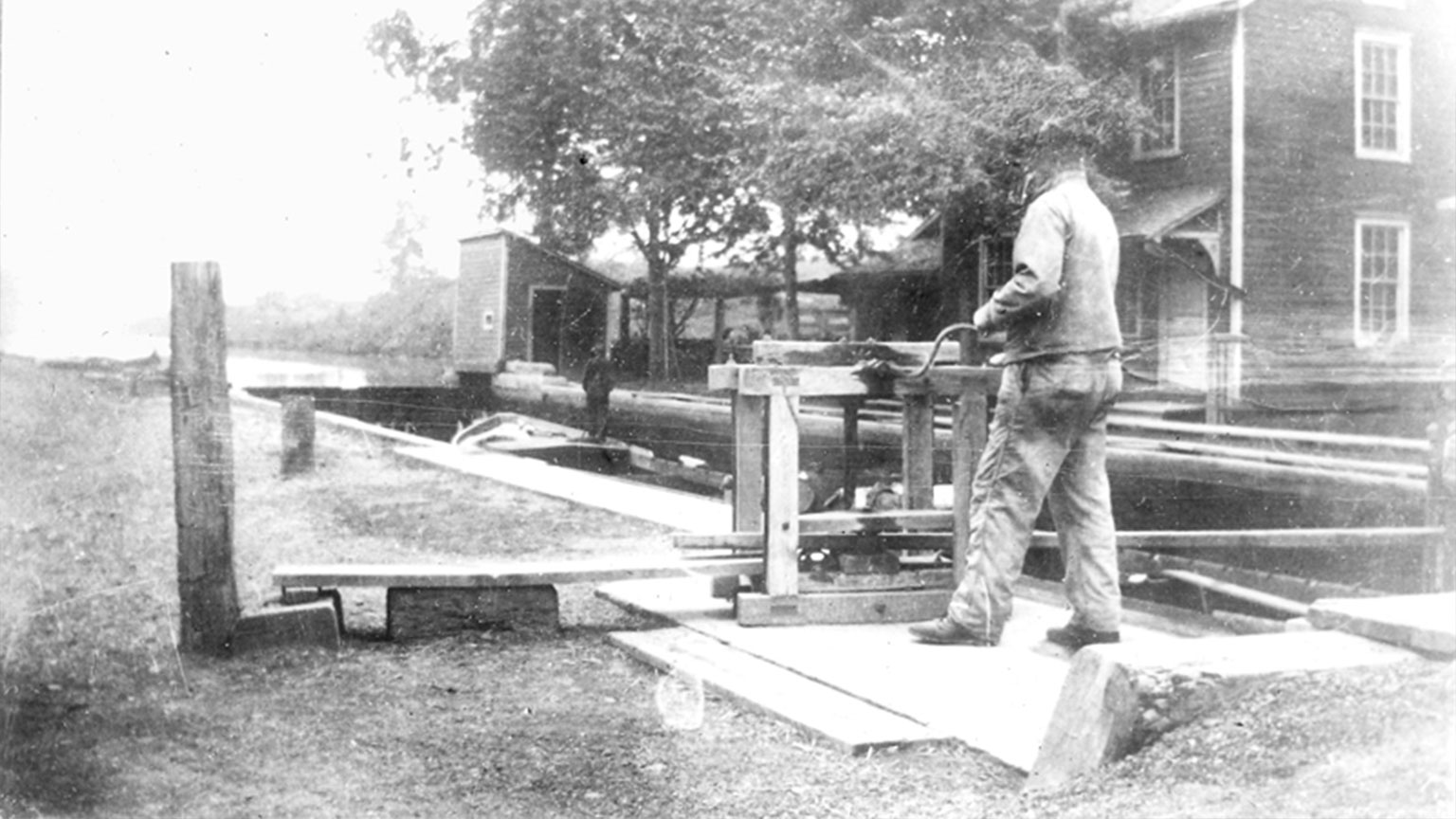 This picture shows a locktender closing the lock.  You can see a canal boat and canal captain in the lock.